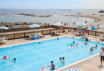 海の近くのプールで遊んでいる人たち