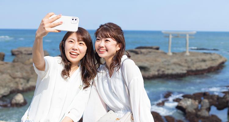 海辺で記念撮影をする2人